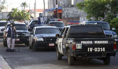 Police outside the home of slain columnist Miguel Ángel López Velasco. His wife and son were also murdered. (AP/Felix Marquez)