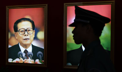 At a Beijing exhibition, a portrait of Jiang and a security guard. (Reuters)