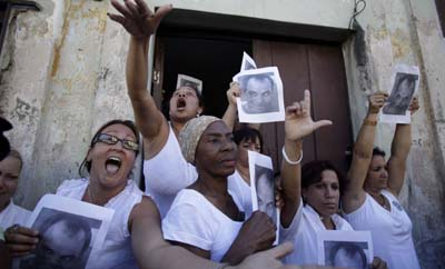 In Cuba, the Ladies in White were instrumental in drawing attention to the plight of imprisoned journalists and dissidents. Here, they hold a photo of Orlando Zapata Tamayo, who died in custody. (AP/Javier Galeano)