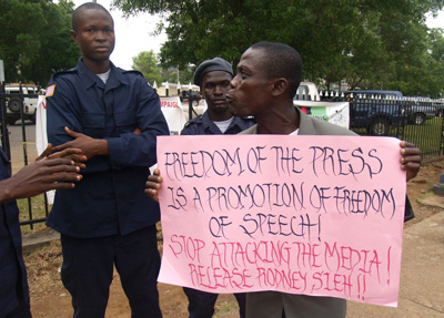 A man in Liberia holds a sign in support of Rodney Sieh, whose newspaper was found guilty of libel. (Aaron Leaf)