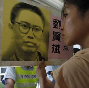 In Hong Kong, a protester holds a portrait of the jailed writer Liu Xianbin. (Reuters)