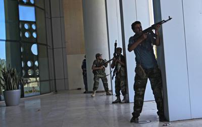 Rebel fighters outside Tripoli's Corinthia Hotel. (AP/Sergey Ponomarev)