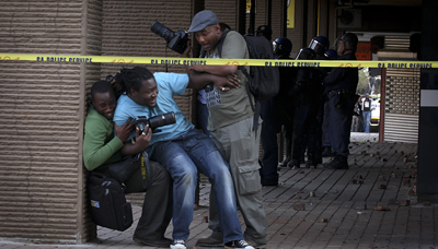 Journalists take cover while Malema supporters protest the ANC leader's disciplinary hearing. (Daniel Born/The Times)