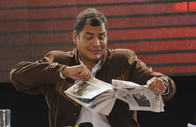 President Rafael Correa rips a copy of the  national daily La Hora during a conference in Cotacachi County. Correa has taken an aggressive stance toward news media. (El Universo)
