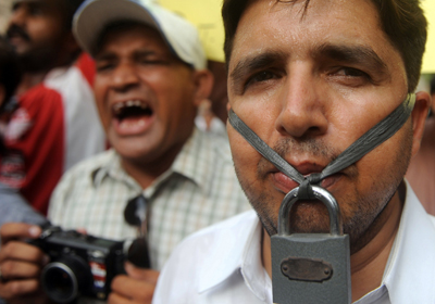 A journalist hangs a lock across his lips during a protest in response to the death of journalist Saleem Shahzad. (AFP)