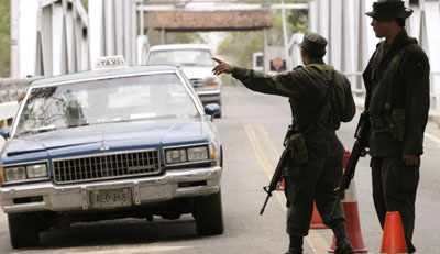 Colombian police officers stop a car at the Arauca City border. (Reuters)
