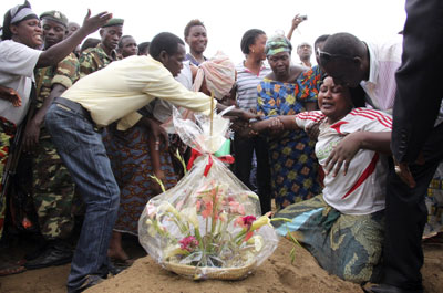 A woman mourns at the burial of a man killed in the Gatumba shooting. (Reuters)
