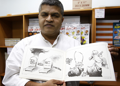 Zunar displays a copy of his previously banned cartoons. (AP)