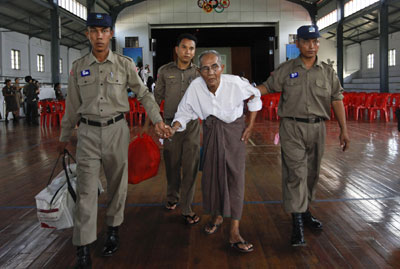 Police assist a newly released prisoner at Insein Prison in Yangon Wednesday. (Reuters)