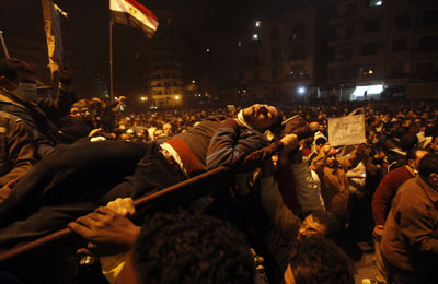 Protesters carry a man wounded during clashes with Egyptian riot police in Tahrir Square Monday, Nov. 21, 2011. (AP)