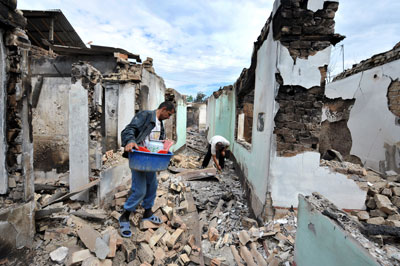 Ethnic Uzbek men look for their belongings at a destroyed house outside Osh on June 16, 2010. (AFP)