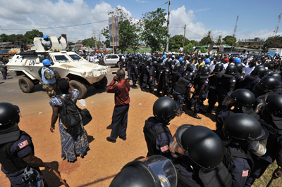 Liberian police face opposition CDC supporters in the run-up to presidential elections. Three broadcasters have been shut down by the government for covering the CDC party's campaign. (AFP)