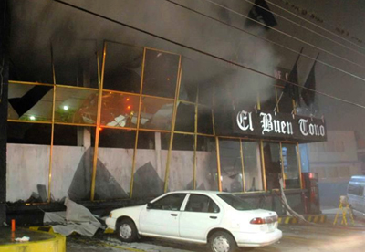 Smoke pours out from the front of the El Buen Tono offices. (Reuters)