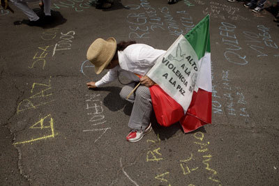 A marcher stops to write a peace slogan during an August 2011 protest against Mexican violence. (AP)