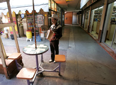 Javier Soto plays his accordion as he searches for tourists in a vacant downtown market in Nuevo Laredo on January 26, 2006. (AP/Gregory Bull)