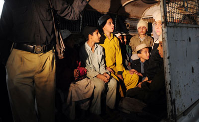 Students are taken away from a Karachi seminary where they were found in chains. Producers from Samaa TV who broke the story have been threatened. (AFP/Asif Hassan)
