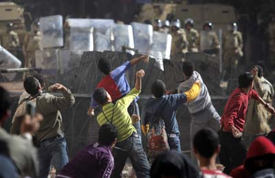 Protesters throw stones at Egyptian soldiers during clashes in Cairo on Sunday. (AP/Nasser Nasser)