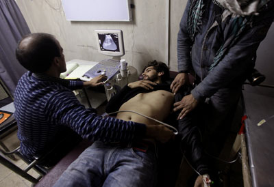 Doctors treat Associated Press cameraman Umar Meraj after he was assaulted by police and paramilitary forces using rifle butts, batons, fists and kicks during a protest in Srinagar on November 25 (AP).