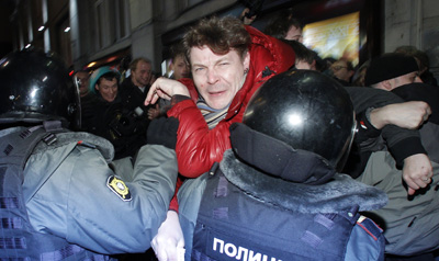 Police officers attempt to detain a journalist from Kommersant during a rally in Russia protesting the results of the parliamentary elections. (Reuters)
