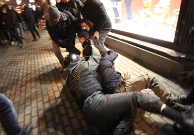 A police officer falls down as he tries to detain a demonstrator during protests against alleged vote rigging in Russia's parliamentary elections in Triumphal Square in Moscow Wednesday. (AP)