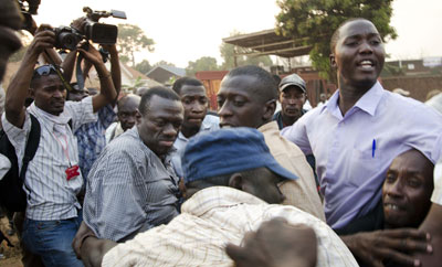 Ugandan opposition leader Kizza Besigye, second from left, is shielded by supporters Tuesday as security personnel try to detain him. Photojournalist Isaac Kasamani is at far left. (AFP/Michele Sibiloni)