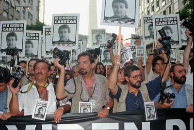 Photojournalists raise photos of José Luis Cabezas as thousands gathered in Buenos Aires on Tuesday, February 25, 1997, to protest Cabezas' murder the previous month. (AP/Daniel Muzio)