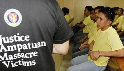 An advocate for the Maguindanao massacre victims appears at a court hearing near several police officers charged in the killings. (Reuters/Romeo Ranoco)