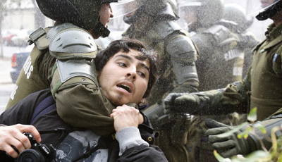 Police in Santiago seize a photographer during an anti-government demonstration. (Reuters/Carlos Vera)