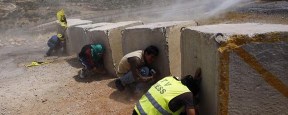 Un journaliste se tapit derrière un bloc de ciment lors d'affrontements entre forces israéliennes et manifestants palestiniens en Cisjordanie. (Reuters / Mohamad Torokman)