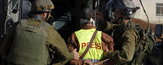 Journalists reporting on protests and civil unrest face a rising threat of detention. Here, Israeli soldiers arrest   a Palestinian journalist. (Reuters)