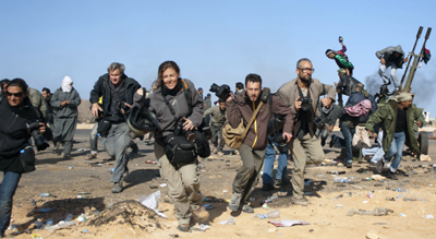 Journalists run for cover during a bombing raid in Ras Lanuf, Libya. (Reuters/Paul Conroy)
