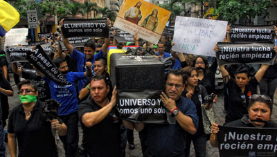 El Universo staff members carry a mock coffin to protest the court ruling that upheld the verdict against their colleagues. (AFP/Camilo Pareja)