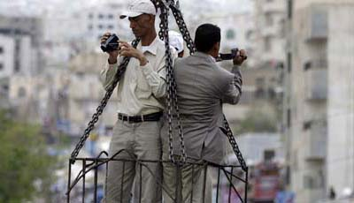 From a crane high above a protest, journalists film crowds in the Yemeni city of Taiz. (Reuters/Khaled Abdullah)