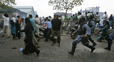 Police chase supporters of former President Mohamed Nasheed, who resigned on Tuesday. (AP/Sinan Hussain)