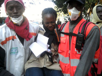 Reporter Sophie Barro is carried by medical personnel after being injured while covering protests on February 17. (Basile Niang)