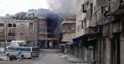 Smoke rises from a building in a Homs neighborhood. The city has been shelled daily for three weeks. (Reuters)