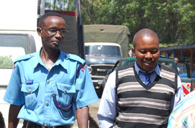 Journalist Suleiman Mbatiah is escorted to the police station where he was detained for almost nine hours. (Courtesy News 24)