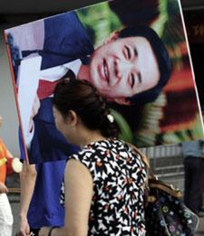 A Chinese woman carries a protrait of Bo Xilai, until recently a rising political star with little tolerance for critics. (AFP)