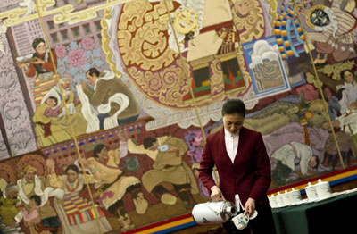 A hostess fills tea cups for delegates inside the Tibet room at the Great Hall of the People before the Tibetan delegation meets as part of the National People's Congress in Beijing Wednesday. (AP/Andy Wong)