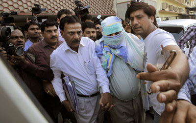 Plainclothes police escort Syed Mohammed Kazmi, an alleged suspect in last month's bombing of an Israeli diplomatic vehicle, from a local court, in New Delhi Wednesday. (AP/Manish Swarup)