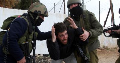 The camera of AFP photographer Musa al-Sha'er was broken by Israeli soldiers shortly after he took this photograph of a protester being detained at a demonstration in the West Bank. (AFP/Musa al-Sha'er)