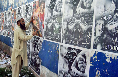 A Pakistani man removes movie posters on a cinema wall in Rawalpindi. (AFP/Abid Zia)