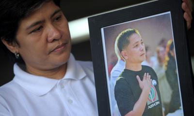 The wife of Philippines journalist Gerardo Ortega looks at his picture. (AFP/Noel Celis)