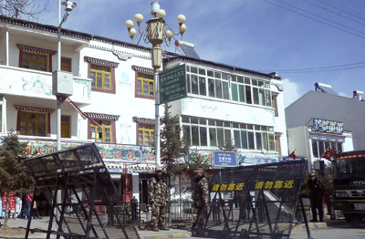 In this photo taken February 27, Chinese paramilitary and riot police stand guard near barricades set up along the main street of a Tibetan monastery town in Sichuan province. (AP/Gillian Wong)