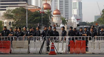 Police officers stand guard during Saturday's protest. (Reuters/Bazuki Muhammad)