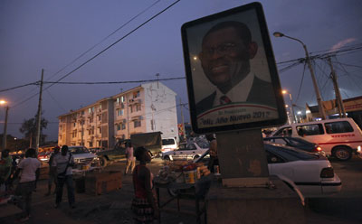 People walk near a portrait of Equatorial Guinea's President Teodoro Obiang along a street in Malabo. (Reuters/Luc Gnago)