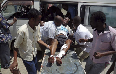 Medical personnel help a man wounded in the explosion in Mogadishu today. (AP/Farah Abdi Warsameh)
