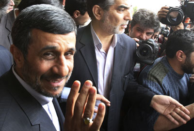 President Mahmoud Ahmadinejad has a wave and a smile for the media, even as his government imprisons journalists under horrific conditions. (AP/Vahid Salemi)