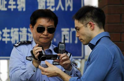 A police officer records the press card of a journalist outside a hospital where Chen Guangcheng is seeking treatment. (AP/Ng Han Guan)