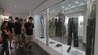 Visitors look at an exhibit displaying the bloodstained clothes of the Jesuit priests murdered by the Salvadoran military in 1989. (AP/Luis Romero)